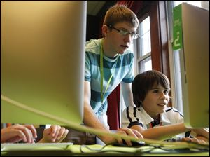 Instructor Thaddeus Owings, left, helps camper Nicholas Sanchez work on creating a video game while at an iD Tech Camp at the Emory University campus, in Atlanta, last week.