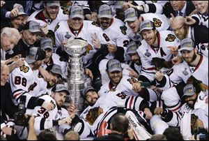The Chicago Blackhawks pose with the Stanley Cup after beating the Boston Bruins 3-2 in Game 6 of the Stanley Cup Final on Monday in Boston.