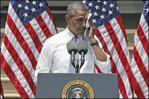 President Obama wipes perspiration from his face as he speaks about climate change  in Washington in June.