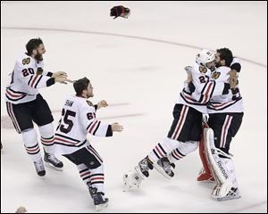Chicago Blackhawks defenseman Johnny Oduya (27) hugs goalie Corey Crawford after winning the Stanley Cup.