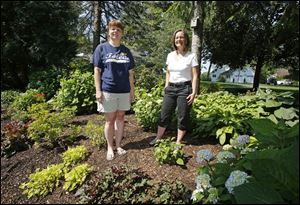 Amy Stolarski, left, and Lyn Tucholski pose in the shared garden between their front yards on Obee Road in Monclova Township.
