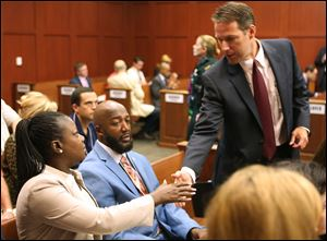The parents of Trayvon Martin, Sybrina Fulton, left, and Tracy Martin, center, are greeted by assistant state attorney John Guy during the George Zimmerman trial in Seminole circuit court, in Sanford, Fla., Monday.