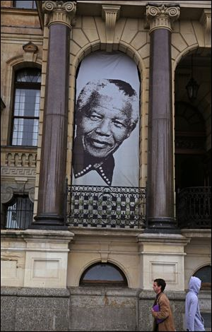 Pedestrian's walks beneath a giant portrait outside the City Hall in Cape Town, South Africa, Monday, June 24, 2013 at the spot where, on the balcony, former South Africa president Nelson Mandela, made his first public speech after being released from 27-years imprisonment.