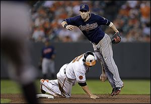 Baltimore's Chris Davis, bottom, breaks up a double-play attempt by Cleveland's Jason Kipnis in the fifth inning on Tuesday.