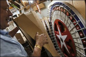 Willis Smith, 81,  shows a gaming wheel he made himself. He built many of the wheels supplied by his and his wife's company because he was unhappy with the quality of those available for purcahse.  out a gaming wheel he hand-made. He and his wife Elaine, 79, are retiring after nearly 40 years of owning and operating their business, Toledo Central Distributors. The pair, who raised eight children in Toledo, say the best part of their business has been working with customers. They have supplied hand made games and amusements for schools, churches and carnivals. Willis built many of the company's at