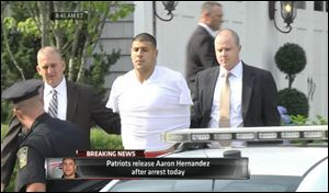 This image from ESPN shows police escorting Aaron Hernandez from his home in handcuffs in Attleboro, Mass., today.