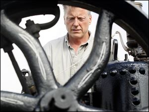 Philip Zuver of the Bryan area works on his 1920 Port Huron steam traction engine during the threshers' 69th reunion.
