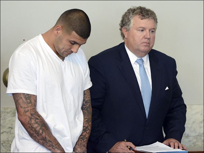 Hernandez Police Football Former New England Patriots tight end Aaron Hernandez, left, stands with his attorney Michael Fee, right, during arraignment in Attleboro District Court Wednesday, in Massachusetts. Hernandez was charged with murdering Odin Lloyd, a 27-year-old semi-pro football player.