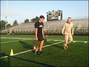 Griffin Janssens, Perrysburg High School junior, finishes his last few yards of Friday morning's football workout with the Marines.
