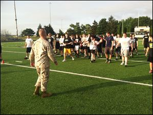 Teammates surround sophomore Zack McKenna as he is the last player to finish the Marine workout Friday morning.