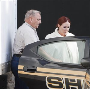 Shannon Richardson is placed into a Titus County Sheriff's car after an initial appearance at the federal building Texarkana, Texas.