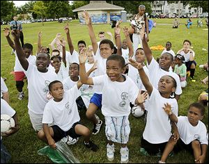 Braylon Ballard, 5, center, and other children get excited while winning prizes during the soccer minicamp at SmithFest.