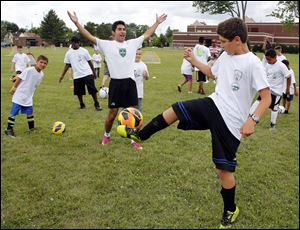 Yadi Aliakbar of the Toledo Celtics Soccer Club, left, cheers as Yasir Jallad, 10, completes a challenge during a mini soccer camp.