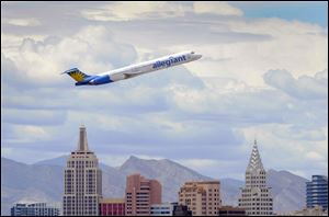 An Allegiant Air jetliner flies over the New York-New York Hotel & Casino after taking off from McCarran International Airport in Las Vegas. The low-cost carrier, based in Las Vegas, relies on additional fees, older aircraft, and lower-than-standard wages.