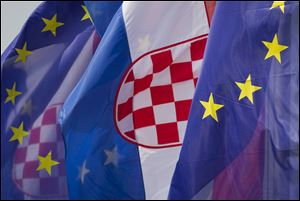Croatian and the EU flags are seen at an intersection in Zagreb, Croatia, Saturday, June 29, 2013. Croatia is to join the European Union on July 1, 2013. (AP Photo/Darko Bandic)