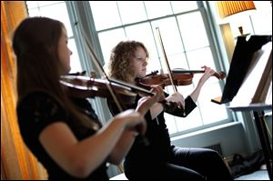 Toledo School for the Arts student Arianna Dyer of Ottawa Hills, right, plays the violin along with student Olivia Bryan of Sylvania during the first 'Noon Tunes' on Friday at the Wildwood Preserve Metropark Manor House in Toledo.
