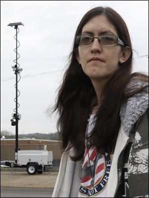 In this Thursday, April 11, 2013 photo, Holly Calhoun stands across the street from a tower of speed cameras located near the Elmwood Quick Stop she manages, in Elmwood Place, Ohio. Calhoun doesn't believe the speed cameras installed in the village were about safety. (AP Photo/Al Behrman)