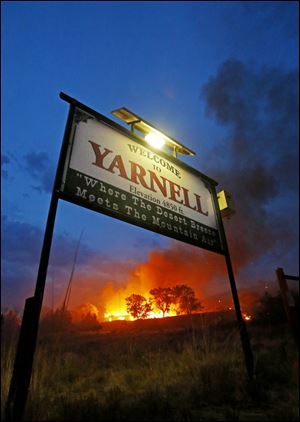 A wildfire burns homes in Yarnell, Ariz. on Sunday. The fire started with a lightning strike on Friday and spread to 2,000 acres on Sunday amid triple-digit temperatures.