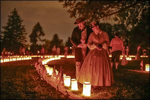 Re-enactors stand near luminaries that mark the graves of Union dead at Soldiers' National Cemetery in Gettysburg, Pa. On July 1, 1863, Union cavalry slowed down the Confederates' advance.