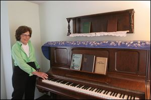 Preservationist Trudy Urbani stands near the historic piano that Ina Duley Ogdon used to write the 1912 hymn 'Brighten the Corner Where You Are' in the very same room of the Century House, Lambertville.