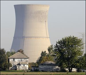 The cooling tower of the Davis-Besse Nuclear Power Station in Oak Harbor, Ohio is seen looming over an adjacent farm.