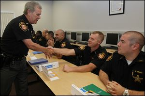 Lucas County Sheriff John Tharp, left, shakes the hand of Corrections Officer Joseph Rowland, as he thanks the officers on Monday during the first day of peace officer training at Owens Community College. Officer Matthew Grant, right, looks on. It's the first class to have to pay its own way.