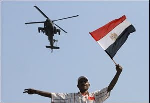 An military helicopter flies over an protester of Egyptian Islamist President Mohammed Morsi as he waves a national flag, in Tahrir Square in Cairo, Egypt.