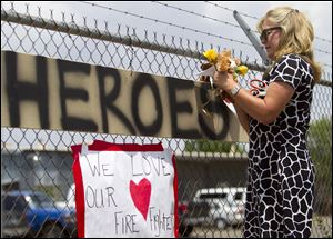 Maggie Greenwood adds flowers to a makeshift memorial at the fire station Monday, in Prescott, Ariz., where an elite team of firefighters was based. Nineteen of the 20 members of the team were killed Sunday when a wildfire suddenly swept toward them in Yarnell, Ariz.