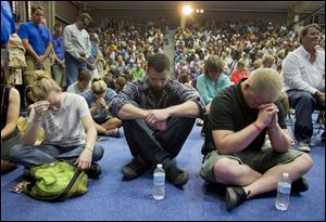 Mourners bow their heads in prayer during a memorial service, Monday in Prescott, Ariz. The service was held for the 19 Granite Mountain Hotshot Crew firefighters who were killed Sunday, when an out-of-control blaze overtook the elite group.