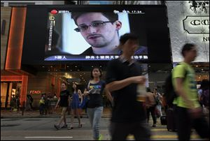 This June 23, 2013 photo shows a TV screen with a news report of Edward Snowden, a former contract employee who leaked top-secret documents about sweeping U.S. surveillance programs, at a shopping mall in Hong Kong.