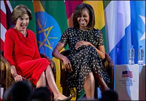 "U.S. first lady Michelle Obama, right, and former U.S. first lady Laura Bush laugh as they participate in the African First Ladies Summit: ""Investing in Women: Strengthening Africa,"" hosted by the George W. Bush Institute today in Dar es Salaam, Tanzania."