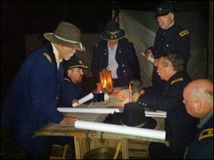 Bob Minton, seated second from right,  strategizes  with other commanding officers during the Blue Gray Alliance's 150th anniversary re-enactment of the Civil War's Battle of Gettysburg.