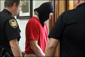 Michael Aaron Fay, his face obscured, is escorted from Juvenile Court after a hearing on Tuesday. He is accused in the deaths of Blaine and Blake Romes, who were 14 and 17, respectively.
