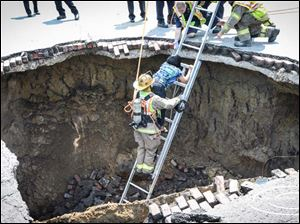 A firefighter helps a woman clime out of a large sinkhole that appeared on North Detroit Avenue near the intersection of West Bancroft Street.