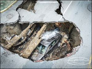 A car sits inside of a large sinkhole on Detroit Avenue.