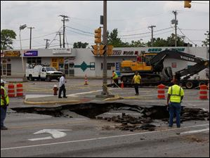 Works stand next to a sinkhole after retrieving the vehicle that had fallen through.