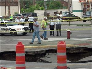 Mayor Mike Bell looks over a large sinkhole that appeared on the street Wednesday. A woman  was  transported to a local hospital after her car plunged into a sinkhole today on North Detroit Avenu.