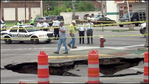 Mayor Mike Bell, far right, examines a large sinkhole that developed on North Detroit Avenue, swallowing a car and its driver.