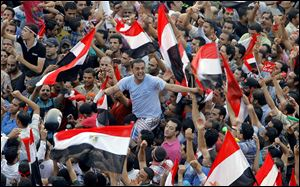 Opponents of Egypt's Islamist President Mohammed Morsi shout and wave national flags in Liberation Square. Army troops, including commandos, have deployed across much of the Egyptian capital.