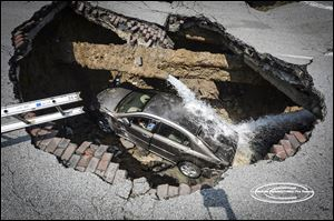 A sinkhole on North Detroit Avenue near Bancroft Street swallowed a car and its driver. Pamela Knox, who was taken to a hospital for examination, was not injured. Officials said a water main had burst as well.
