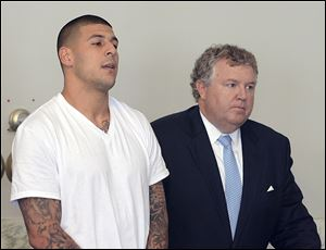 Aaron Hernandez, left, stands with his attorney, Michael Fee, right, during arraignment in Attleboro District Court in Attleboro, Mass.