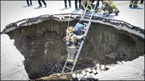 The motorist whose car fell into the sinkhole is helped out.