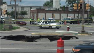 A big sinkhole on N. Detroit Avenue swallowed a car and briefly trapped a motorist.