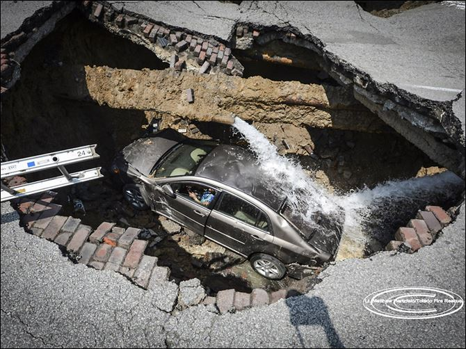 04n5sinkhole A sinkhole on North Detroit Avenue near Bancroft Street swallowed a car and its driver. Pamela Knox, who was taken to a hospital for examination, was not injured. Officials said a water main had burst as well.