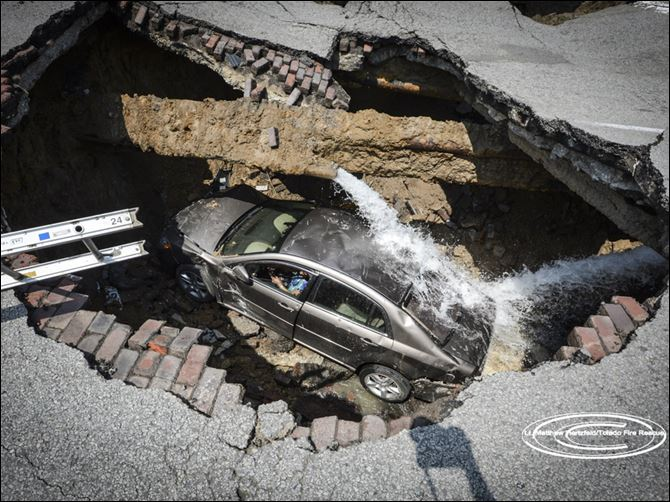 sinkhole 1.jpg This sinkhole swallowed up a car on N. Detroit Avenue.