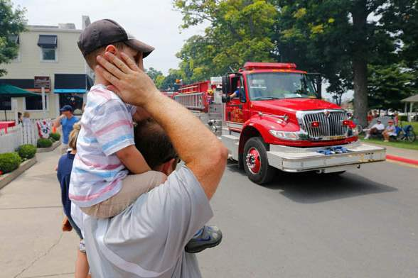 Justin-Severino-Eastlake-Ohio-covers-the-ears-of-his-son-Max-2-as-a-fire-truck-roars-past-during-a-Salute-to-America-Parade