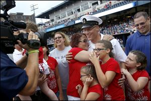 Chief Petty Officer David Schuster, center, is hugged by his mother, Pat Ricard of Berkey, as he is welcomed home by his extended family at Fifth Third Field.