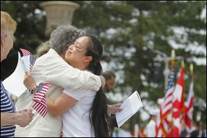 Kim Thi Tran of Lima, Ohio, originally from Vietnam, gets a hug from Nancy Mills of the Daughters of the American Revolution, Fort Industry Chapter, at a naturalization ceremony on South Bass island.