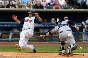 The Mud Hens' Matt Tuiasosopo ducks the tag as he slides home safely in the bottom of the fourth inning, when Toledo scored three times. He has reached base in five of his eight at-bats with Toledo.