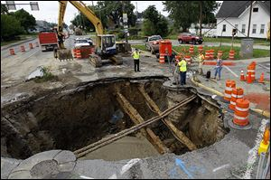 Workers assess the area of the sinkhole July 5, 2013 at the intersection West Bancroft Street and North Detroit Avenue in Toledo